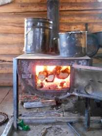A half-barrel stove in one of our cabins