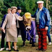 Souzz's parents flanking a purple cow